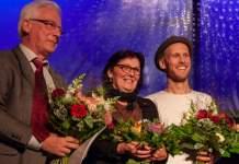 Zwei Männer und eine Frau stehen auf der Bühne