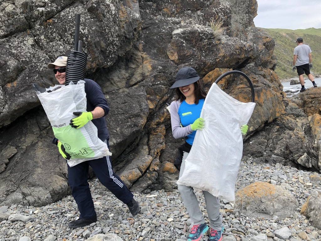 Photo of two people carrying bags of rubbish by some rocks