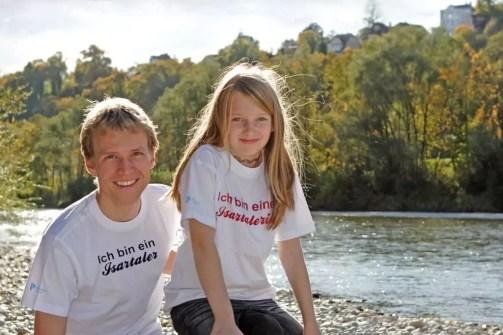 Mann und Mädchen tragen Pullach T-Shirts und lächeln in die Kamera, im Hintergrund die Isar