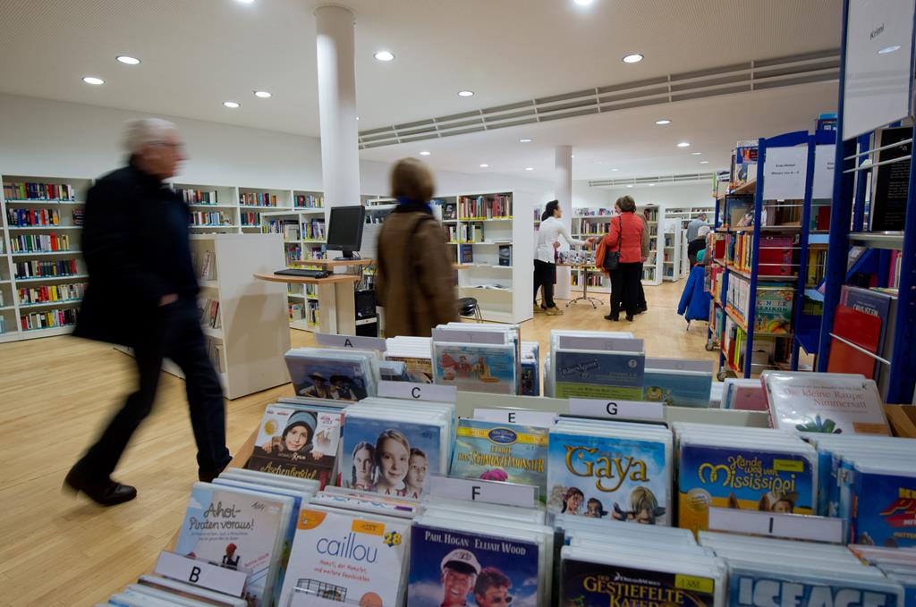 Bücher und DVD-Regale in der Bücherei. Kunden gehen den Mittelgang entlang und werfen einen Blick auf die Regale und einen Infotisch