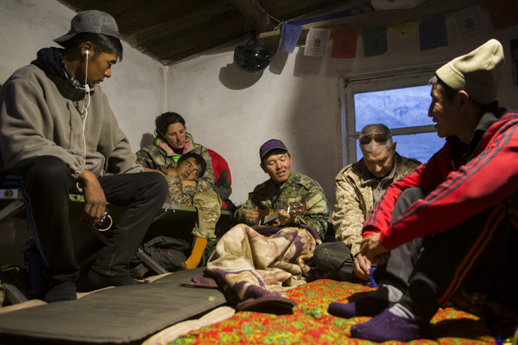 Rangers Temirlan Baktygul, Urmat Solokov, Anne-lise Cabanat, Michel Gierst, Temirbek Jandrbaev listening to Ulan Abulgaziev playing the ukulele, Sarychat-Ertash Strict Nature Reserve, Tien Shan Mountains, eastern Kyrgyzstan relaxing in camp during evening, Sarychat-Ertash Strict Nature Reserve, Tien Shan Mountains, eastern Kyrgyzstan