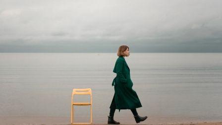 chi organizza viaggi per single? foto di ragazza con cappotto verde e una sedia in viaggio da sola