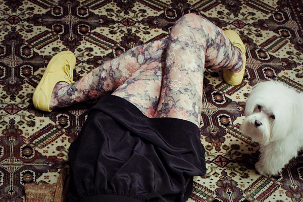Urban Outfitters floral tights and yellow soled sneakers on carpet.
