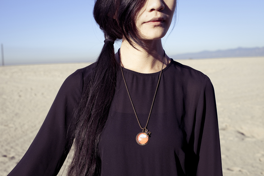 Detail of my etsy narwhal necklace and H&M black chiffon dress.