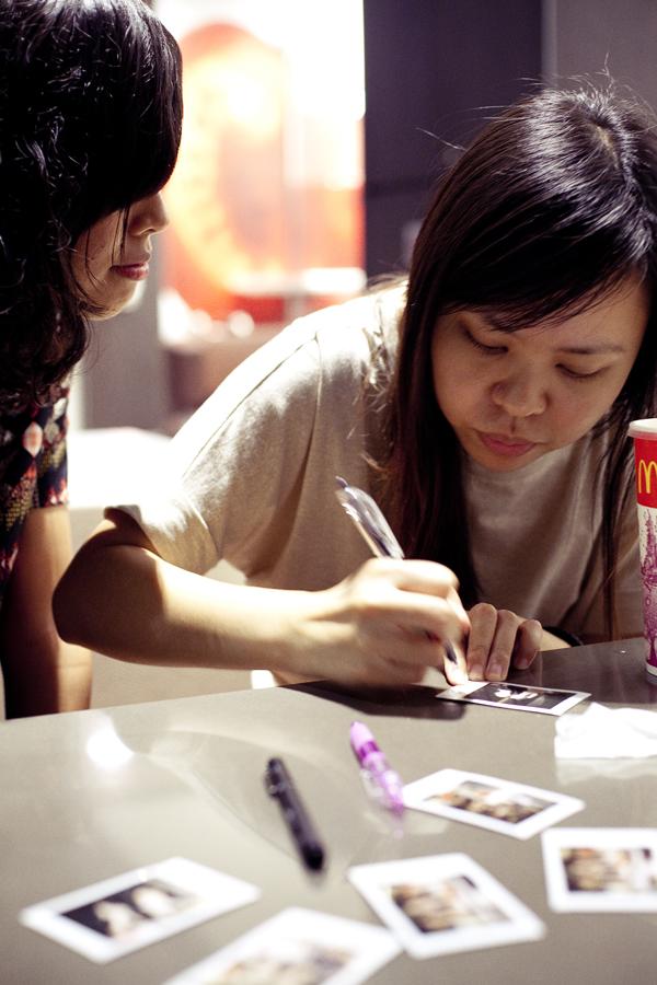 Shasha and Ruru at Macdonald's writing on Instax photos.