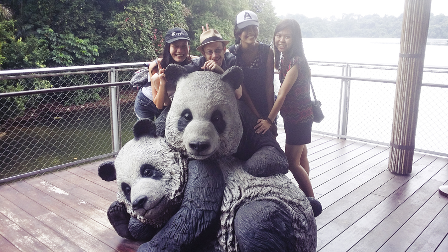 Friends and I posing with panda statues at the River Safari.