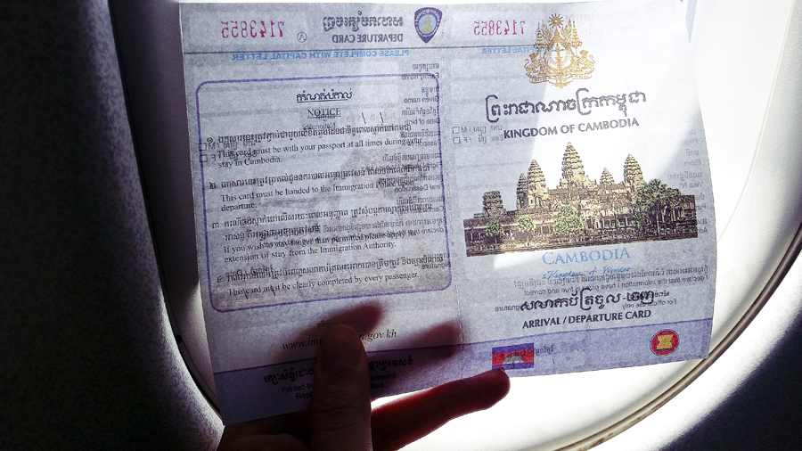 On a plane, holding an arrival card to enter Cambodia.