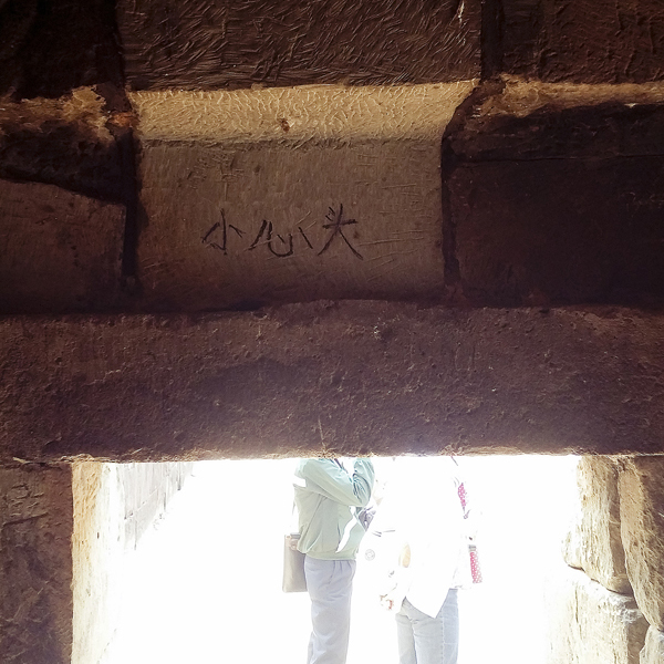 Sign written in Mandarin into the top of the low opening to be mind your head.
