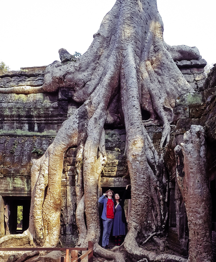Ottie and Ren at a structure engulfed by a tree at Ta Prohm, Cambodia.