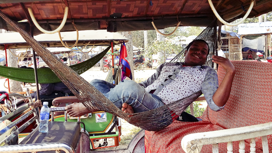 Tuk-tuk driver relaxing on a hammock in Cambodia.