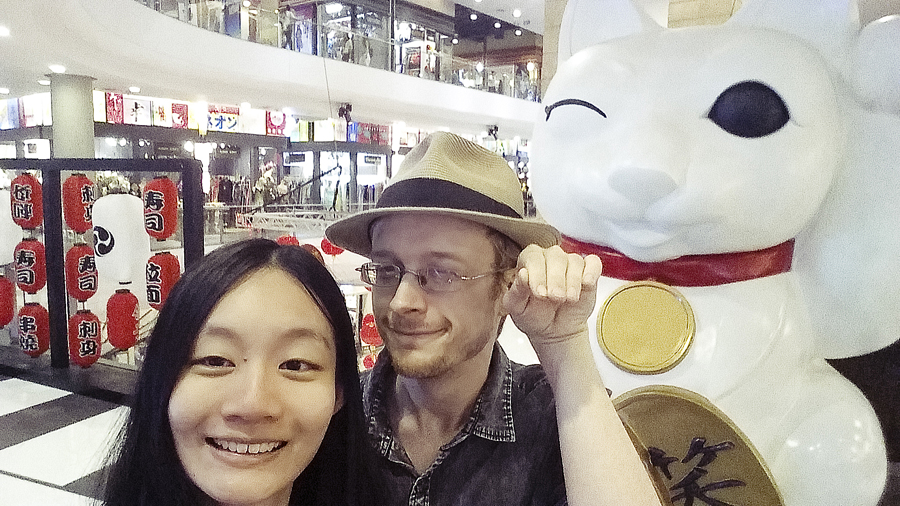 Ren and Ottie posing with a Maneki Neko fortune cat statue in Terminal 21 in Bangkok, Thailand.