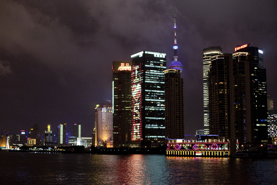 Lit-up buildings of the Shanghai skyline at night by the Bund.