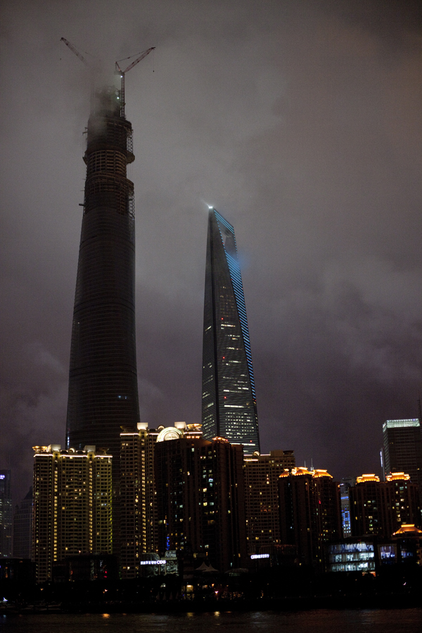 Buildings of the skyline at the Bund in the fog of the night, Shanghai.