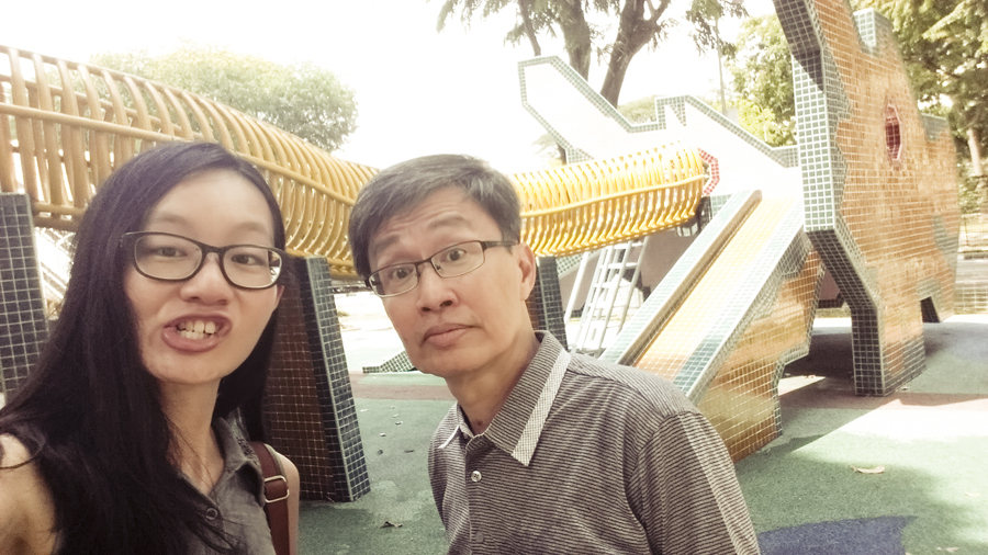 Ren and Pa making funny faces at a playground.