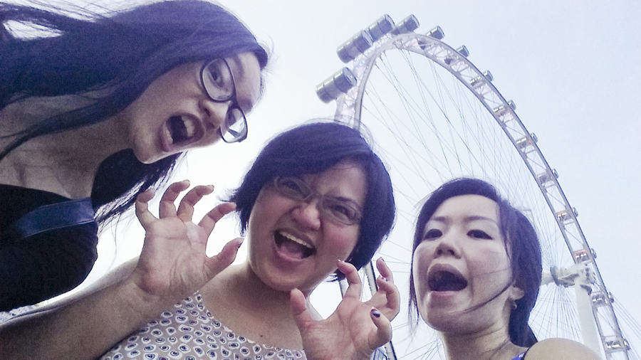 Ren, Puey, and Ade making funny scary faces in front of the Singapore Flyer.