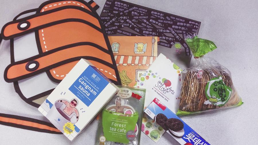Orange 2D sling bag and korean snacks and tea and goodies on my desk.