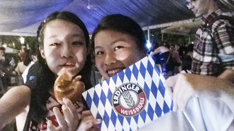 Ren holding a pretzel and Deb holding an Erdinger flag at the Oktoberfest The Beer Garden at the Fullerton Hotel.