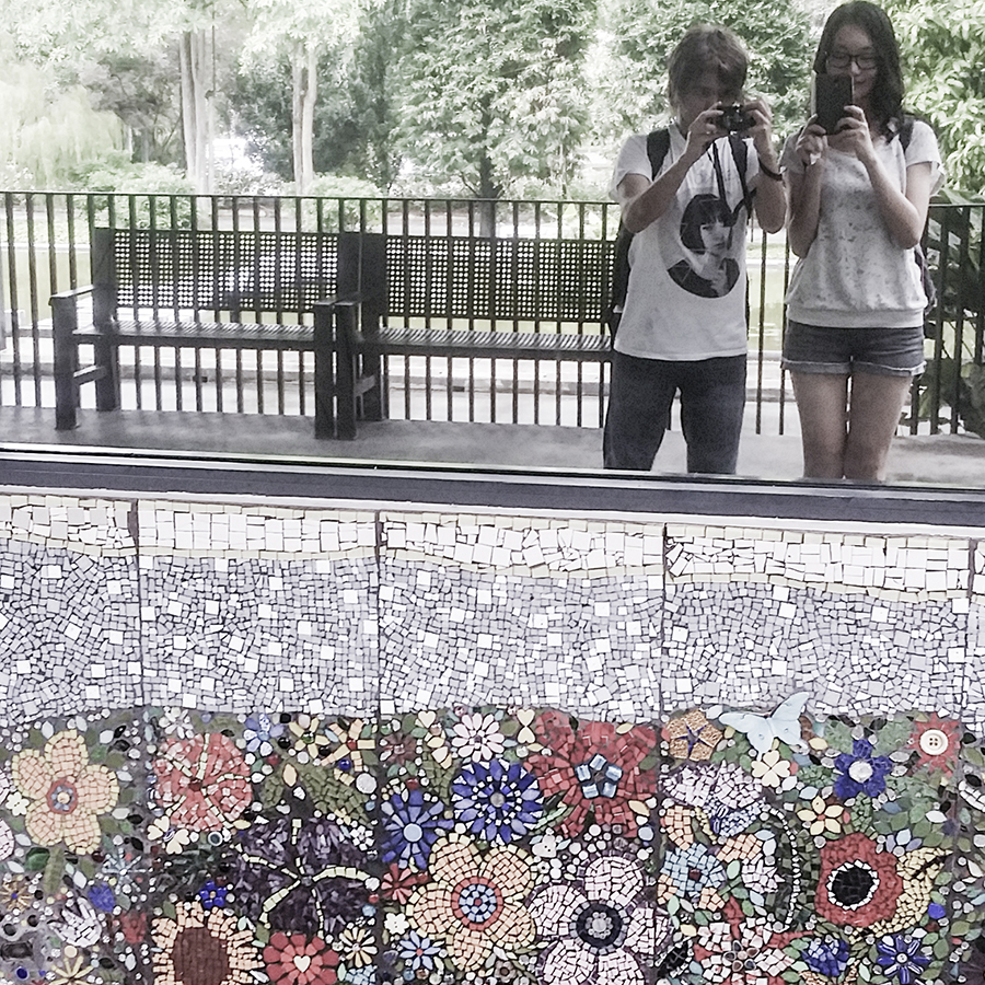 Mirror shot of Shamis and Ren and a mosaic wall at the Hort Park, Singapore.