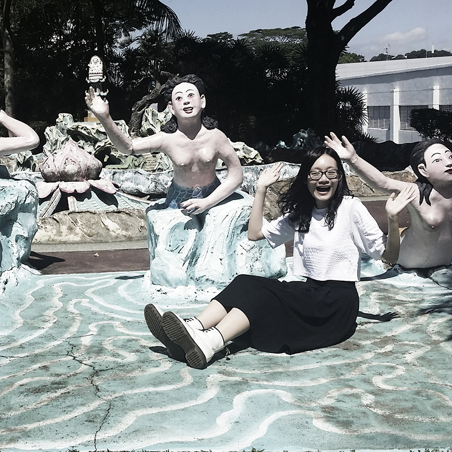 Posing with weird mermaid statues at Haw Par Villa, Singapore.