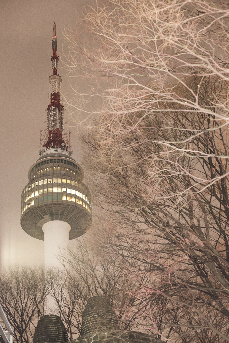 Namsan tower in pink lighting at night.