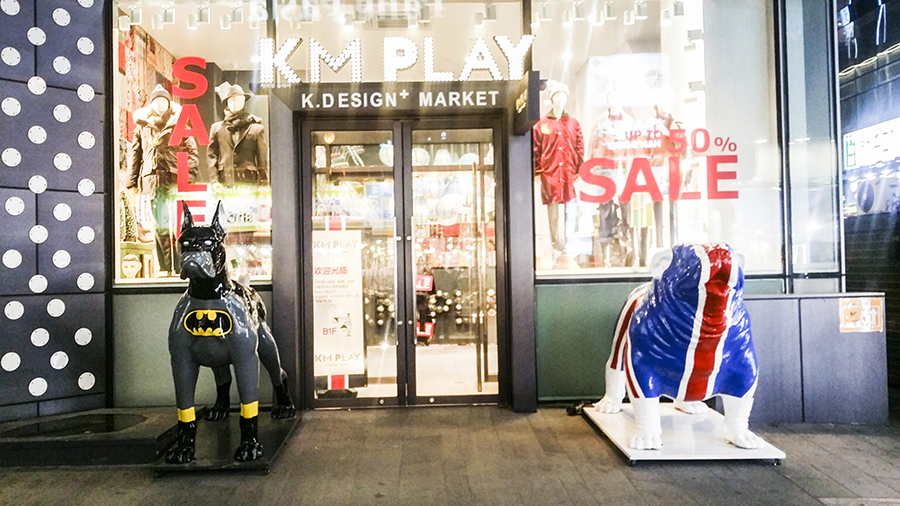 Cute batman-painted doberman statue and Union Jack flag bulldog statue outside a store in Myeongdong, Seoul, South Korea.
