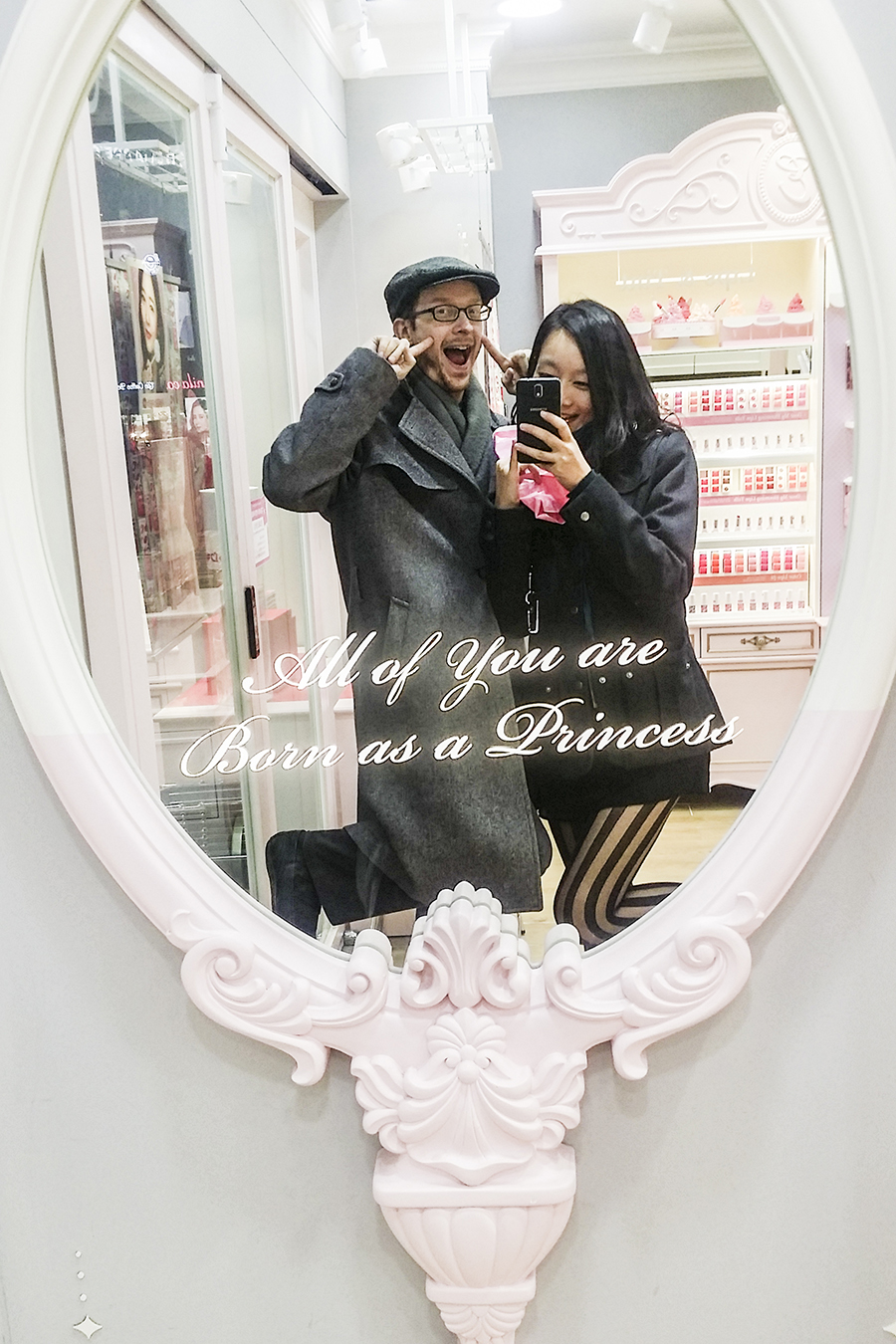 Ottie and Ren posing in front of a mirror at Etude House with the inscription: All of you are Born as a Princess, in Myeongdong, Seoul, South Korea.