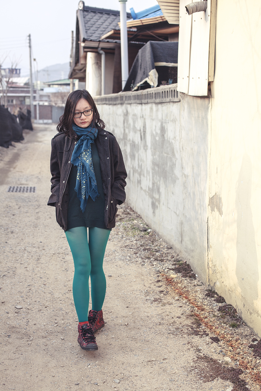Outfit in green: H&M merino wool sweater in green, Marshalls blue shawl with gold studs, teal tights, H&M men's jacket, black rimmed Gap glasses, Twisted Sisters eye motif Caren Bracelet via Zalora, Alexander McQueen x Puma high top sneakers.