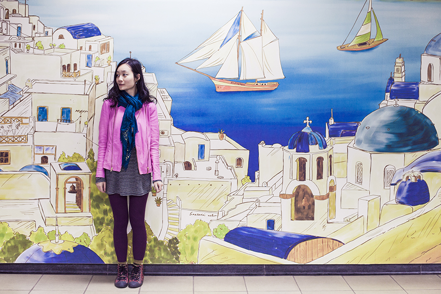 Outfit in front of a mural of Santorini, Greece on Seoul subway station, South Korea: Viparo pink leather jacket, Marshalls gold studded shawl, Zara striped dress, Hue ribbed tights, Alexander McQueen x Puma red sneakers.