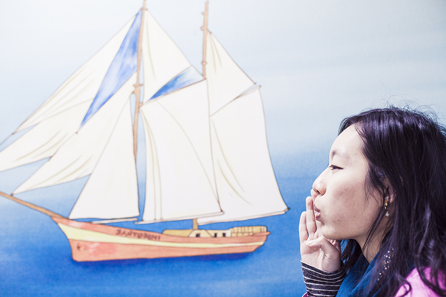 Blowing on the sails of a painted ship of Santorini on a mural in Seoul subway, South Korea.