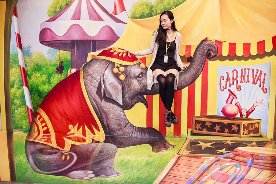 Sitting on a circus elephant's trunk at a trompe-l'œil at the Trick Eye Museum Renewal Event in Singapore, Resorts World Sentosa.
