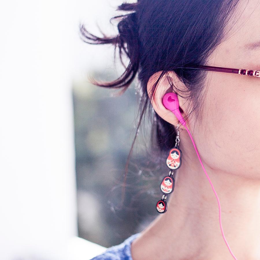 Matryoshka earrings and hot pink iLuv earphones.