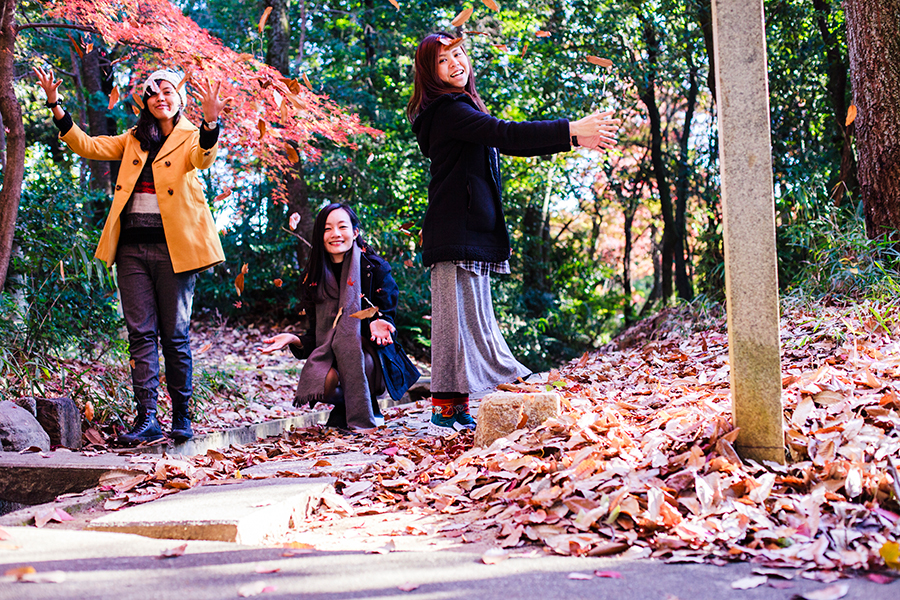 Shasha, Ren, and Ruru throwing dried maple leaves in the air.