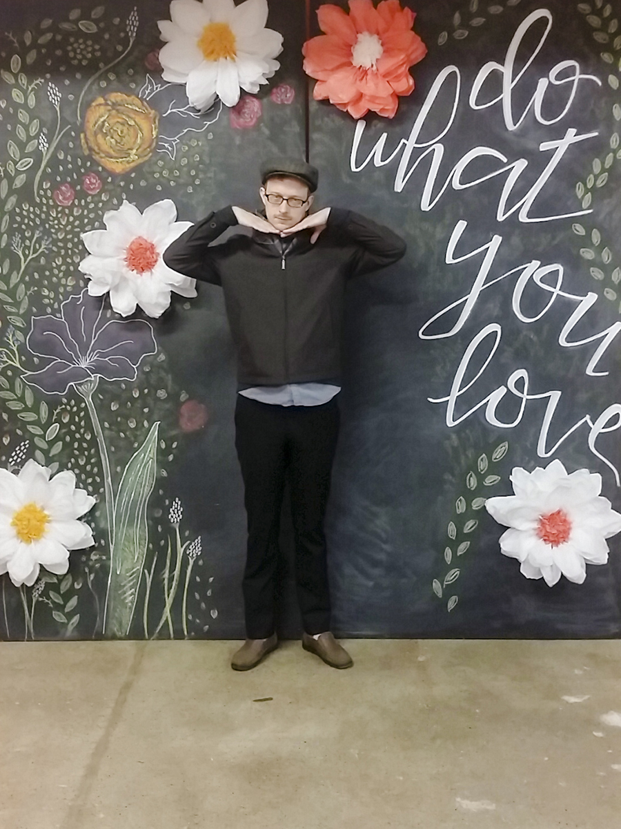 Ottie posing in front of blackboard 'Do What You Love' calligraphy and florals at Unglued craft fair.