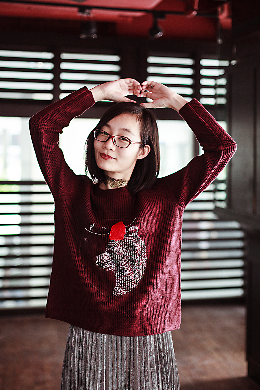 Making a heart shape with my arms in my bear sweater.