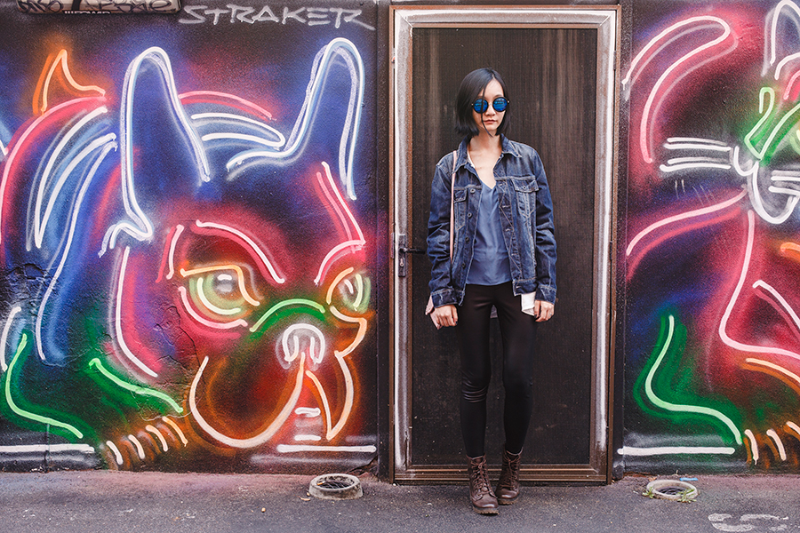 Denim leather outfit in front of a neon lights mural in Perth Australia.