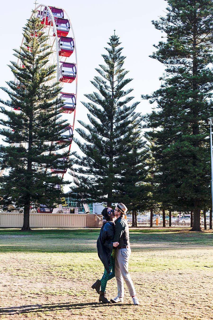 Couple photo in front of a ferris wheel Fremantle Perth Australia.