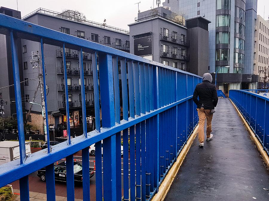 Walking on a blue overhead bridge in Harajuku, Tokyo.