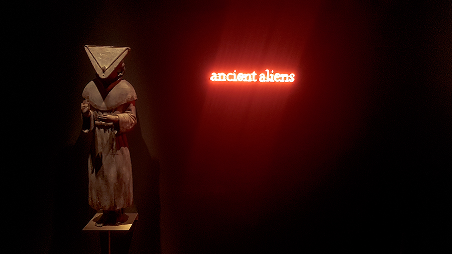 Prêtre JÔMON wood sculpture and Ancient Aliens neon sign by Laurent Grasso at the The Universe and Art: An Artistic Voyage Through Space exhibition, ArtScience Museum Singapore.