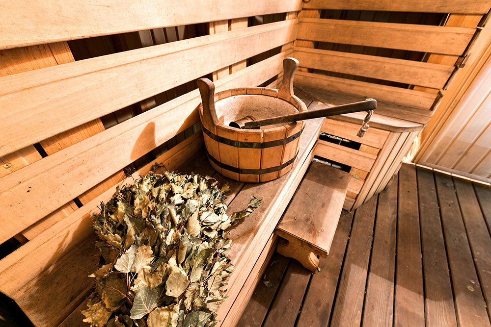 Hot wooden sauna room with ladle