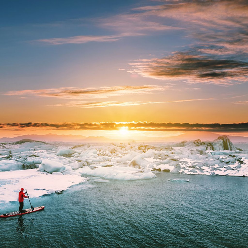 Landscaped, Beautiful glacier lagoon in sunset with a guy paddle boarding