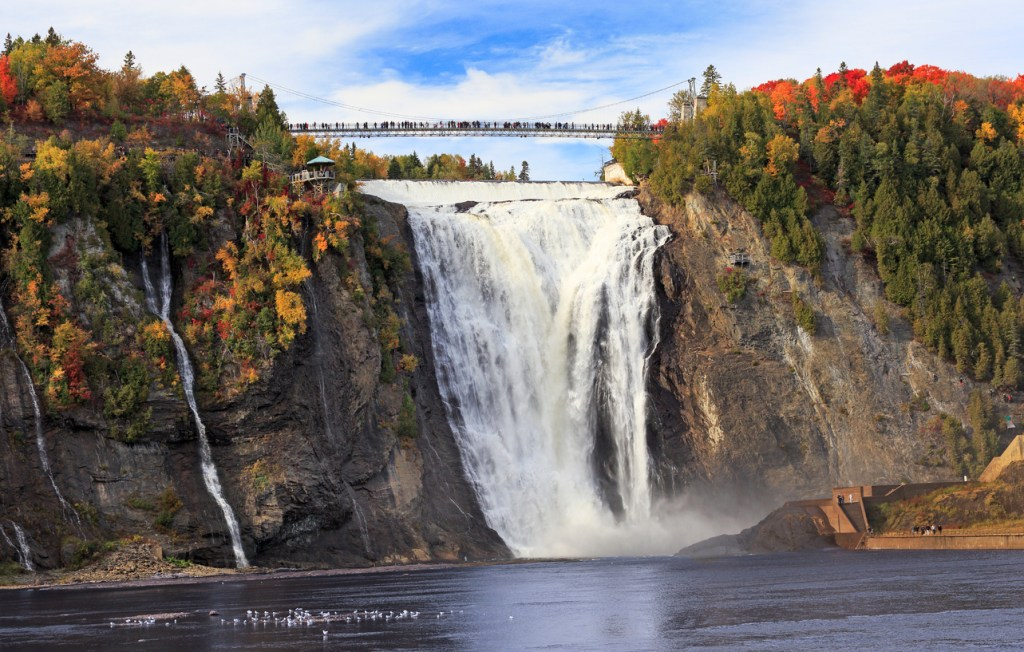 Montmorency Falls and Bridge in autumn with colorful trees, Quebec, Canada