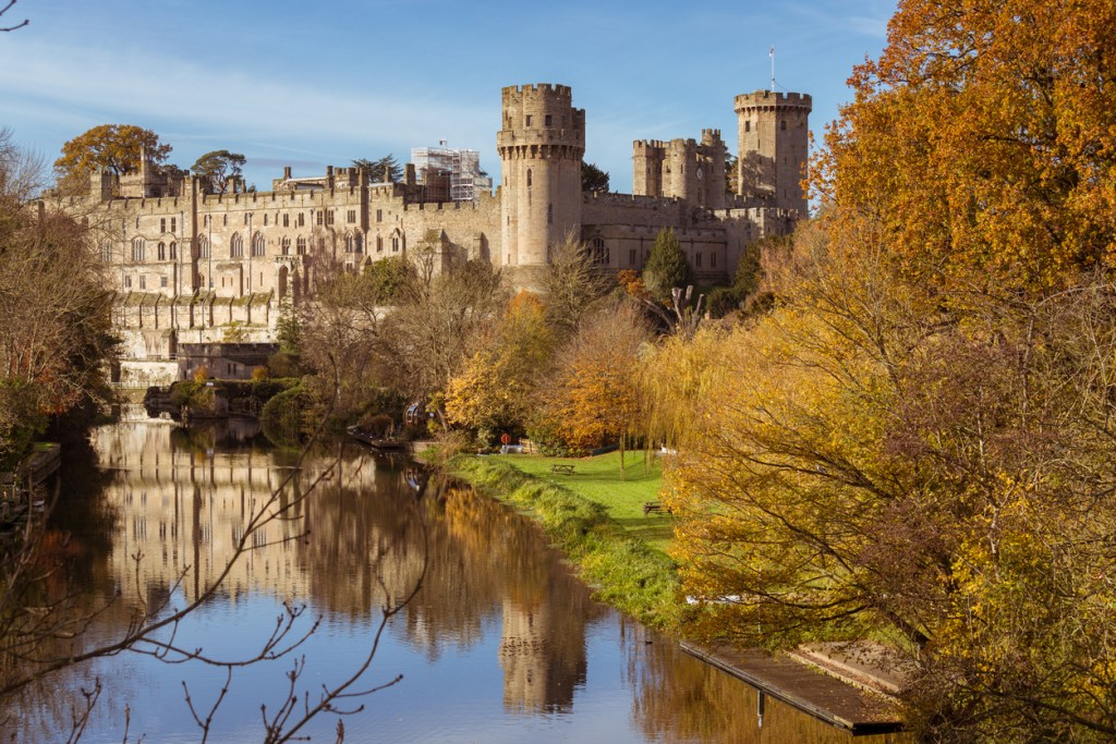 Warwick castle on the river Avon warm autumn day with fall colours