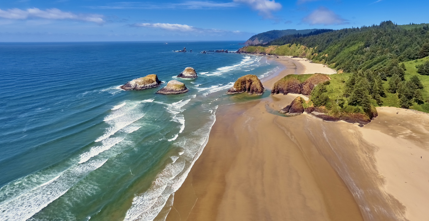 Aerial panorama shot at approximately 350 feet above Cannon Beach looking towards Ecola State Park on a sunny blue sky day on the Oregon Coast
