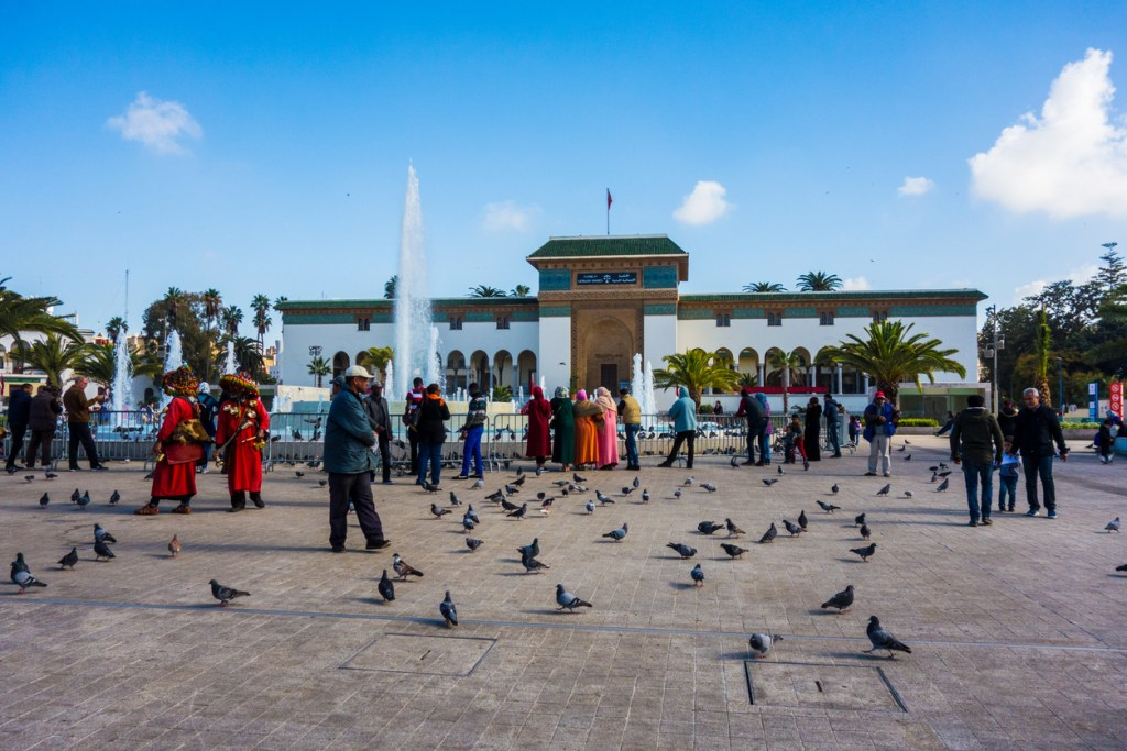 Moroccan water seller in traditional dress, and people walking around the Palace of Justice on Mohammed V Square in Casablanca