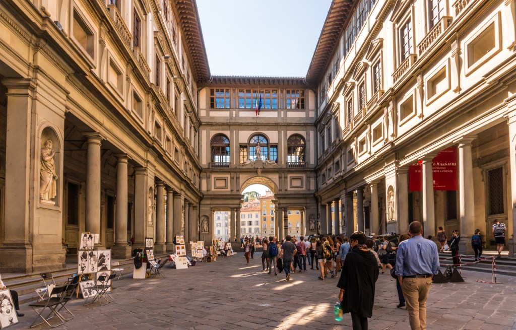 Tourists browsing through The Uffizi Gallery Museum in Florence, and walking toward the Arno river.