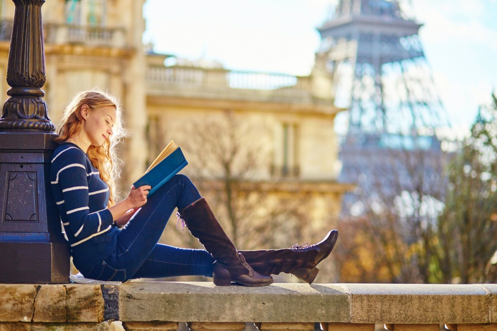 A beautiful young woman in Paris, reading a book