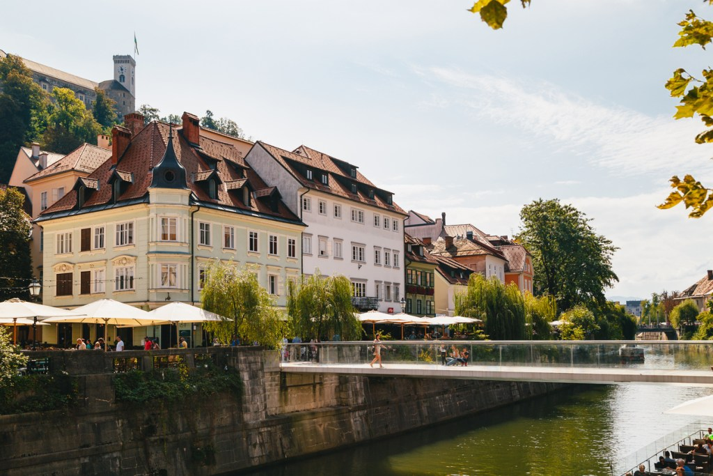 A beautiful view at river Ljubljanica, Cankarjevo Nabrezje, bridges and Ljubljana Castle tower, the tourist centre of Ljubljana, the capital of Slovenia. With people relaxing in cafes at the both banks of the river