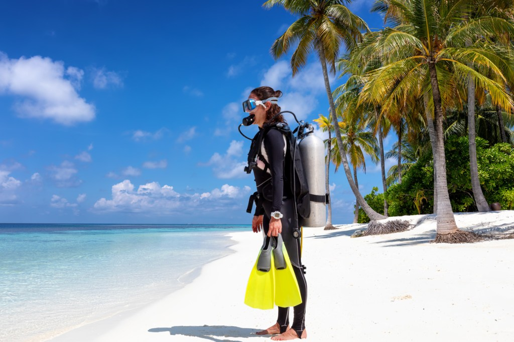 Scuba Diver in Full Equipment Stands on a Tropical Beach