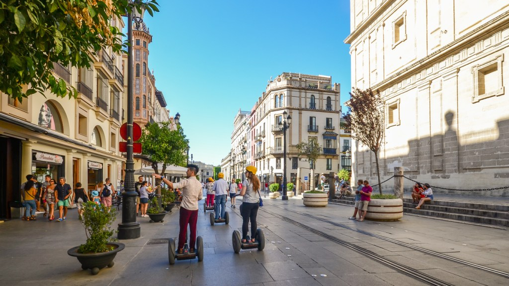 Tourists on segways at Av. de la Constitucion in the historic centre of Seville, Andalusia, Spain