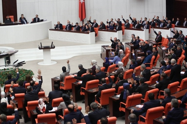 Lawmakers raise their hands to offer a vote of confidence for the news government at the parliament in Ankara, November 30, 2015. / AFP PHOTO / ADEM ALTAN